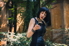 Pretty goth girl using phone in a city park Royalty Free Stock Image