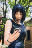 Pretty goth girl using phone in a city park Royalty Free Stock Photos