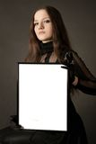 Pretty gothic girl with blank frame. Pretty gothic girl in black dress with blank frame in hands over gray background Stock Photo