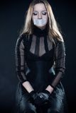 Pretty gothic girl in corset. With sealed mouth looking down Stock Photo