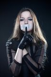 Pretty gothic girl in corset with sealed mouth. Over dark background Royalty Free Stock Images