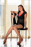 Pretty graceful woman. In black clothes sitting on the chair Stock Images
