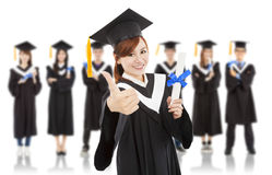 Pretty graduation student thumb up with classmates Royalty Free Stock Photography