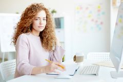 Pretty graphic designer elaborating maquette. Serious confident pretty young female graphic designer with red curly hair elaborating maquette according to stock images
