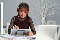Pretty Graphic Designer Wrapped up in Work. Waist-up portrait of pretty Asian graphic designer sitting at office desk and listening to music in headphones while Stock Photography