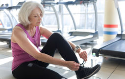 Pretty gray haired woman tying shoelaces in a gym. Time to go home. Concentrated pretty senior woman tying shoelaces and listening to music while sitting on a stock image