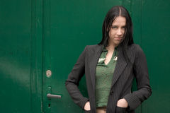 Pretty in Green. Beautiful Girl in casual business suit against a green wall / background Royalty Free Stock Image