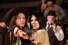 Pretty Gunfighters. Two pretty cowgirls point revolvers at the camera Stock Photos