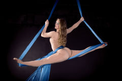 Pretty gymnast training on aerial silk. Pretty gymnast training flexibility on aerial silk royalty free stock photos