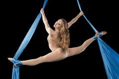 Pretty gymnast training on aerial silk. Pretty gymnast girl training flexibility on aerial silk stock images