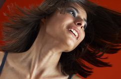 Pretty Hair Blowing. Portrait of a young woman in a studio setting with hair freely blowing in the wind against a reddish background Royalty Free Stock Photos
