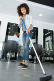 Pretty hairstylist sweeping hair clippings on floor in salon. Pretty hairstylist sweeping hair clippings on floor in her salon Royalty Free Stock Photography