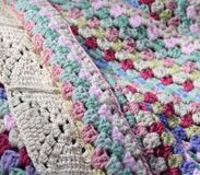 Pretty handmade crochet afghan wool blanket. Details of different stitch types, vintage shades of creams, pinks, blues and green yarns, a craft and hobby stock photo