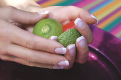 Pretty hands. French Manicured hands holding lemon and lime  with purple background Stock Photo