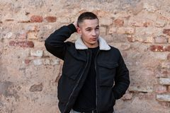 Pretty handsome young man in a fashionable black jacket with a white collar in a T-shirt with a stylish hairstyle poses. Near a brick old building. Attractive royalty free stock images