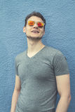 Pretty handsome young man hipster with sunglasses smiling laughing behind blue wall. Looking aside. Toning. royalty free stock image