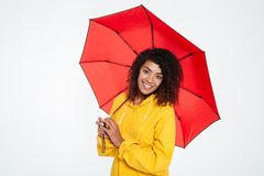Pretty happy african woman in raincoat posing with umbrella Royalty Free Stock Photography