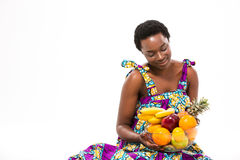 Pretty happy african woman sitting and looking at fresh fruits Stock Photo