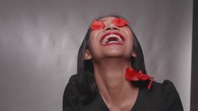 Pretty happy girl having fun with confetti with isolated over gray wall. Pretty happy Asian girl having fun with confetti with isolated over gray wall background stock video footage