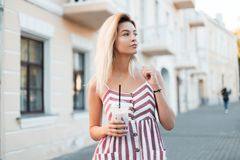 Pretty happy beautiful young blond woman in a fashionable pink striped dress with a sweet milk drink near a building in the city. Beautiful pretty girl model royalty free stock photo