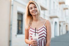 Pretty happy beautiful young blond woman in a vintage pink striped dress with a sweet cold milk drink walk on the street. Near a buildings. Urban joyful  girl royalty free stock photography