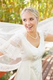 Pretty happy blonde bride holding her veil out Royalty Free Stock Images
