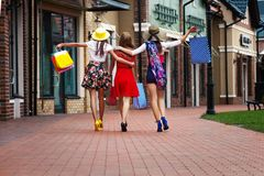Happy women friends tourists in shopping mall. Pretty happy bright women female girls friends in colorful dresses, hats and high heels with shopping bags walking stock images