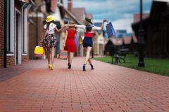 Fashion female women friends in shopping mall. Pretty happy bright women female girls friends in colorful dresses, hats and high heels with shopping bags walking royalty free stock photography