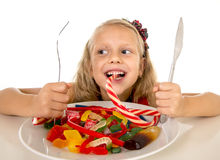 Pretty happy Caucasian female child eating dish full of candy in sweet sugar abuse dangerous diet Royalty Free Stock Photography