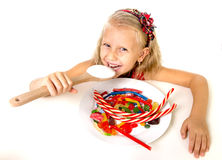 Pretty happy Caucasian female child eating dish full of candy in sweet sugar abuse dangerous diet Stock Photos