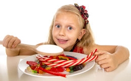 Pretty happy Caucasian female child eating dish full of candy in sweet sugar abuse dangerous diet Stock Images