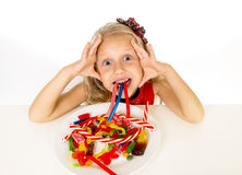 Pretty happy Caucasian female child eating dish full of candy in sweet sugar abuse dangerous diet Royalty Free Stock Image