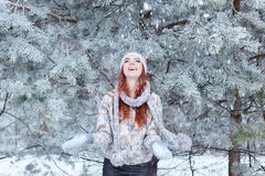 Pretty happy cheerful beautiful young girl with hair rydimi fun in the snowy woods and enjoys first snow in hat with scarf Royalty Free Stock Photos