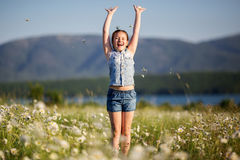 Pretty happy child girl at camomile field Stock Photos