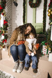 Pretty happy family sitting in front of door decorated on Christmas Stock Photos