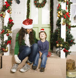 Pretty happy family sitting in front of door decorated on Christmas Royalty Free Stock Image