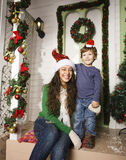 Pretty happy family sitting in front of door decorated on Christmas Royalty Free Stock Photography