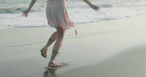 Pretty happy girl in dress relaxing on the sandy beach stock video