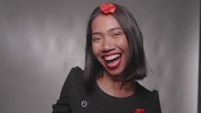 Pretty happy girl having fun with confetti with isolated over gray wall. Pretty happy Asian girl having fun with confetti with isolated over gray wall background stock video