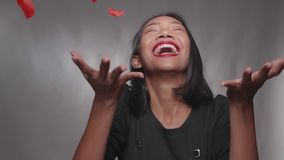 Pretty happy girl having fun with confetti with isolated over gray wall. Pretty happy Asian girl having fun with confetti with isolated over gray wall background stock footage