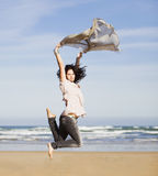 Pretty happy girl jumping. Beautiful happy young girl running and jumping over a windy beach with a blowing scarf Stock Photography