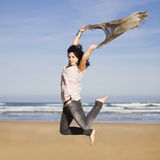 Pretty happy girl jumping. Beautiful happy young girl running and jumping over a windy beach with a blowing scarf Royalty Free Stock Photography