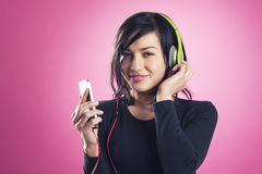 Pretty happy girl listening to music with earphones. Stock Images