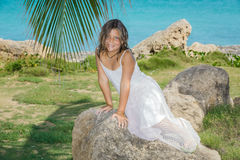 Pretty happy girl looking mermaid sitting on the rocks in tropical garden Royalty Free Stock Photos