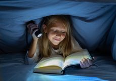 Pretty happy girl reading a book in darkness hiding under the duvet in bed with flash light stock photos