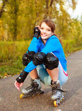 Pretty happy girl with rollerskates Stock Photos