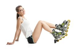 Pretty happy girl with rollerskates sitting on Royalty Free Stock Photo