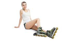 Pretty happy girl with rollerskates sitting on Royalty Free Stock Images