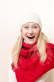 Pretty happy girl wearing red knitted scarf and gloves looking in surprise Stock Photo