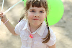 Pretty happy little girl holds green balloons at sunny day Royalty Free Stock Images